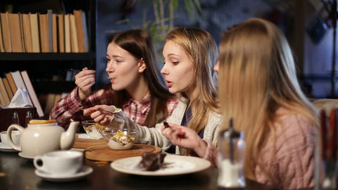 Two young teenage girls eating desserts in cafe Footage
