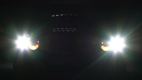 Auto switches on bright headlight, car emerges in darkness suddenly, danger Footage