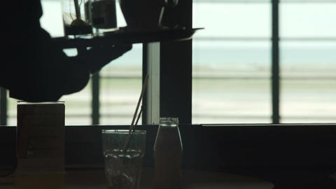 Cafe at the airport, waitress putting glass and coffee cups on table, service Footage