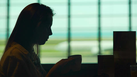 Beautiful woman waiting for plane in airport restaurant and drinking coffee Footage