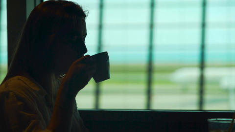 Young lady sitting in airport restaurant and enjoying hot coffee, tourism Footage