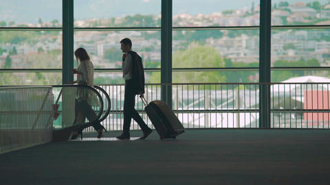 Business trip, man and woman walking to escalator in airport, carrying luggage Footage