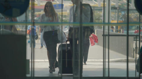 Man and woman in long dress enter airport hall through automatic opening doors Footage