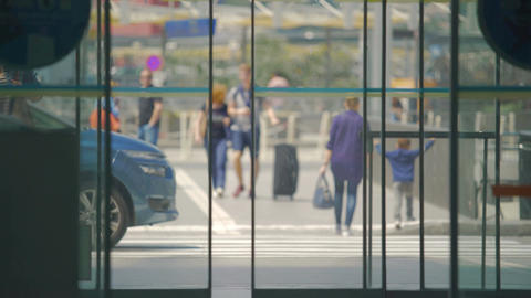 Busy city life, view on pedestrians through airport doors, tourism and travel Footage