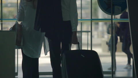 Female and male travelers walking out through airport automatic opening doors Footage
