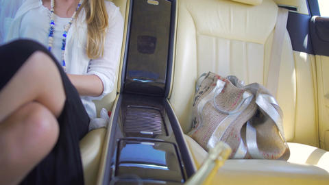 Beautiful rich female sitting on backseat of luxury car, enjoying vacation Footage