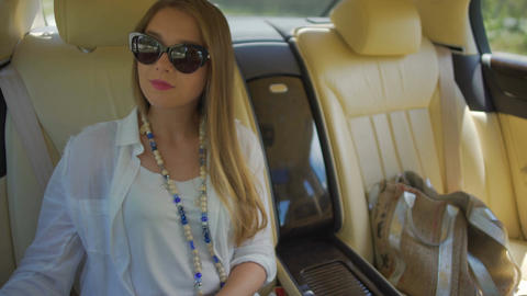 Beautiful young female in sunglasses sitting in elite taxi and enjoying view Footage