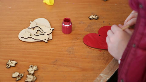 Craft and maker class, child coloring wooden heart, hobby, handmade course Footage