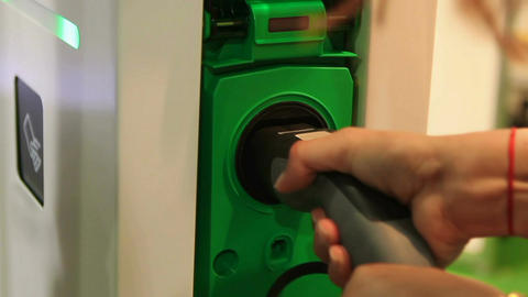 Driver plugging electric vehicle in socket, using services of charging station Footage