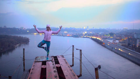 Brave young woman standing in yoga pose on the top of bridge, dangerous hobby Footage