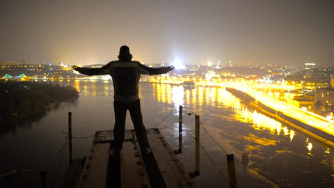Meditation on the edge of bridge at night, man enjoying fantastic view on city Footage