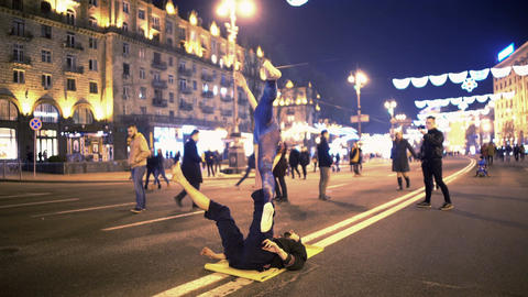 Male and female doing acro-yoga on the street in city center, hobby, sport Live Action