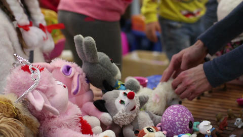 People selling soft toys at charity garage sale, raising funds to help children Footage