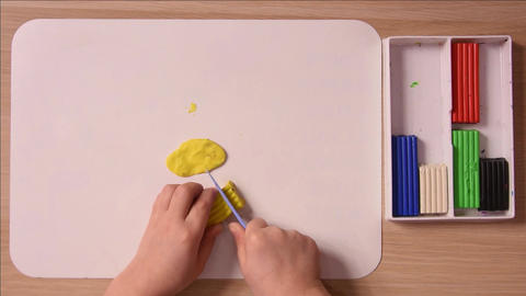 The child cuts off a piece of a stack of yellow plasticine for crafts, close-up, Footage