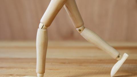 Wooden figurine walking on wooden floor Live Action