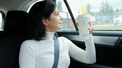 Woman sitting in car holding disposable cup Footage