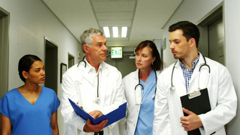 Doctors and nurse discussing over medical report while walking in corridor Footage