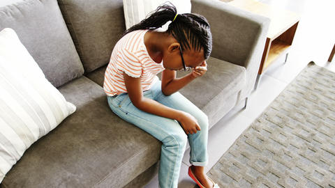 Upset girl sitting on sofa in corridor Footage