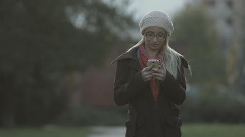 Woman sms texting on smart phone at park Footage
