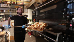 Baker pulls pastries tray from the oven Footage