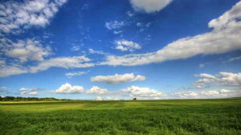 4K. Timelapse clouds over the green field. FULL HD, 4096x2304 Footage