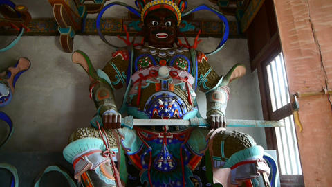 Chinese immortals Buddhist Vajra sculpture holding a sword in carved beams paint Footage