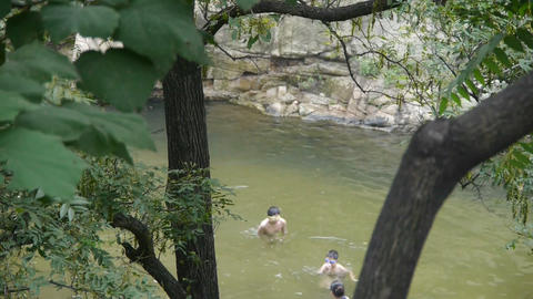 People swimming in lake,dense forests Stock Video Footage