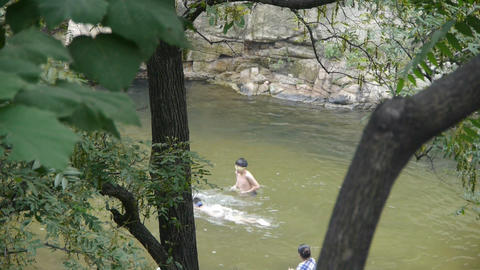 People swimming in lake,dense forests Footage