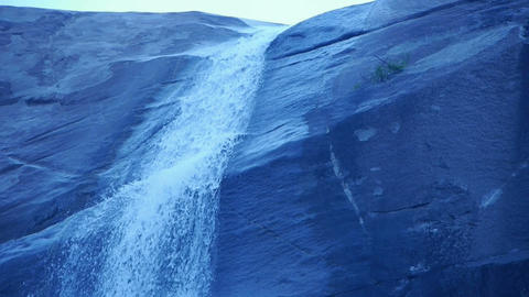 waterfall on cliffs in mountains,flowing into pond lake Stock Video Footage