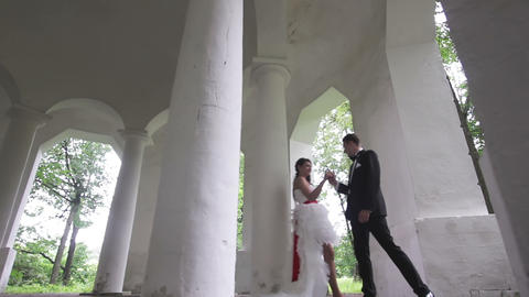 Bride and groom dancing in the ancient columns Footage