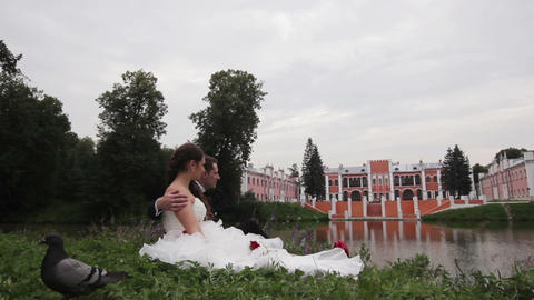 Bride and groom are sitting on grass in the park Footage