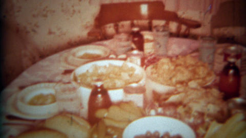 1966: Table of party food spread with chips dips breads olives grapes and soup.  Footage