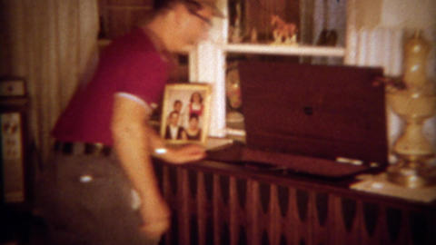 1966: Dad plays music chest vinyl record player for guest's listening pleasure.  Footage