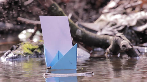 Blue paper boats drifted on a dirty water puddles 80a Footage