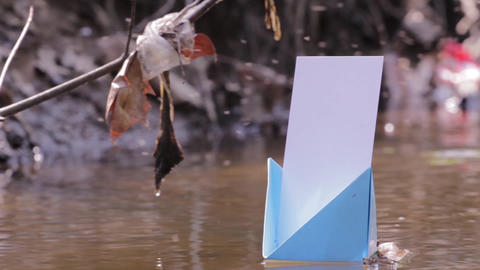 Blue paper boats drifted on a dirty water puddles 80 Footage