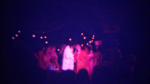 1973: Women kissing and hugging sleazy entertainer after pop music performance.  Footage