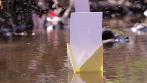 Colored paper boats drifted on a dirty water puddles 81 Footage