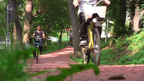 Group of cyclists descend on sloping driveway of the forest 32b Footage