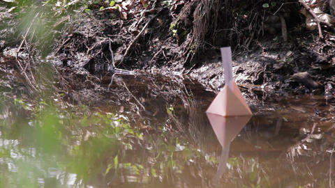 Paper prow floating adrift on the water of a river 64 Footage