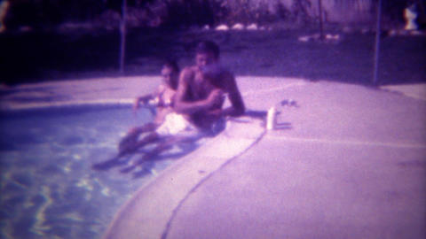 1972: Leathery suntan man smoking in pool with young bikini clad companion. SAN  Footage
