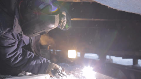 Man Welds Machine Components in Arctic Footage