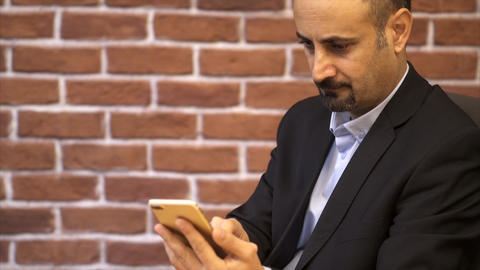 Business man using smart phone - Brick wall background Footage