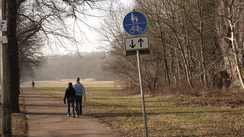Couple Walking In Park Away From Sign Footage