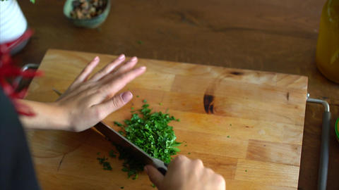 Woman chopping parsley on a wooden table in kitchen Footage