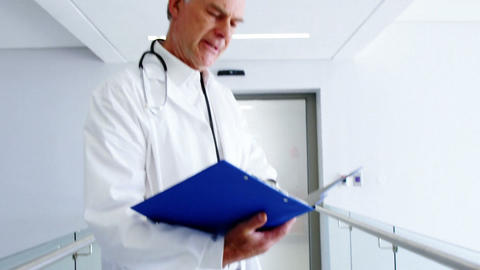 Doctor looking at medical report and smiling at camera Footage