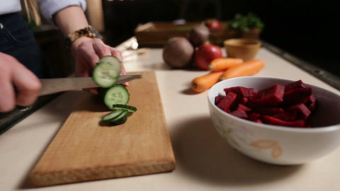 Female hands with knife cutting cucumber on board Footage
