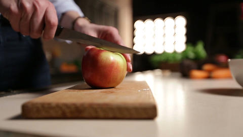 Woman with knife cutting apple on chopping board Footage