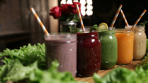 Various freshly blended smoothies on wooden tray Live Action