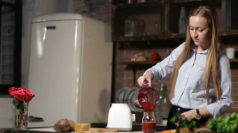 Woman pouring beet smoothie from blender into jar Footage