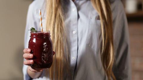Female hand holding fresh beet smoothie in jar Footage